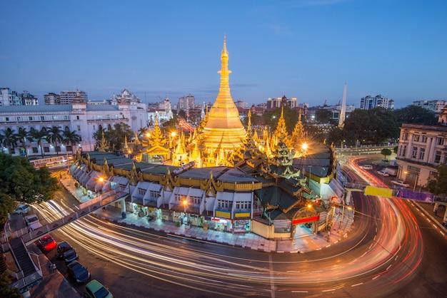 Yangon, de oude hoofdstad van myanmar. yangon-verkeer met lange blootstelling aan de beroemde bezienswaardigheid van sule pagoda na zonsondergang yangon, myanmar