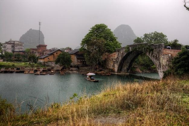 Yangshuo, guangxi, china dragon bridge over yulong river, spring regen maakt de toeristen nat tijdens een riviercruise op een bamboevlot, het gebied van karstheuvels in het pittoreske guilin.
