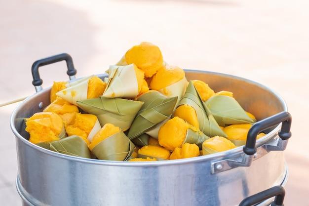 Yellow toddy palm cake met witte kokos in de stalen steaming pot.
