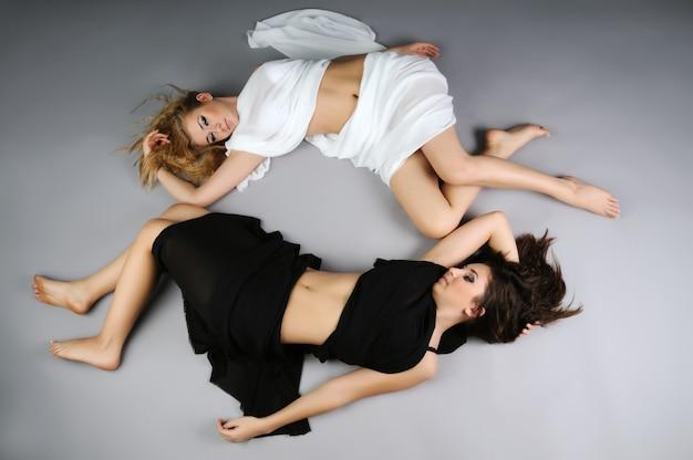 Yin-yang-symbool. bovenaanzicht van twee jonge mooie slanke meisjes in zwart-wit liggen met hun lichamen tegen elkaar en personifiëren de tegenstellingen die altijd dichtbij zijn.