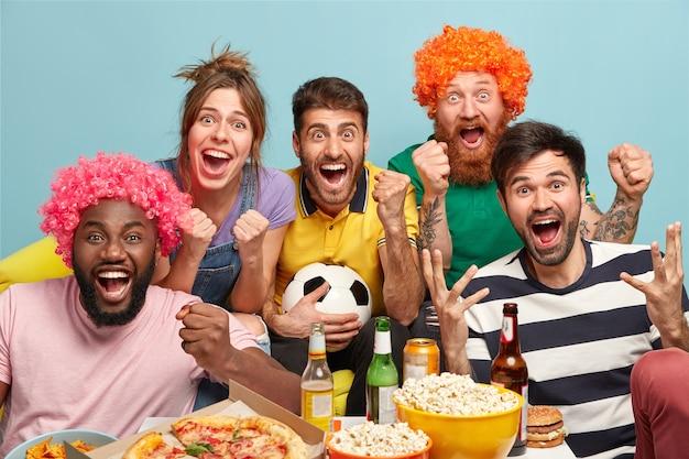 Yippee, ons team wint. blije jongens en vrouwelijke supporters drukken wilde opwinding uit, voelen geluk, vieren de overwinning, hebben koud bier, snacken, heffen gebalde vuisten op, hebben weekend, geïsoleerd op een blauwe muur.
