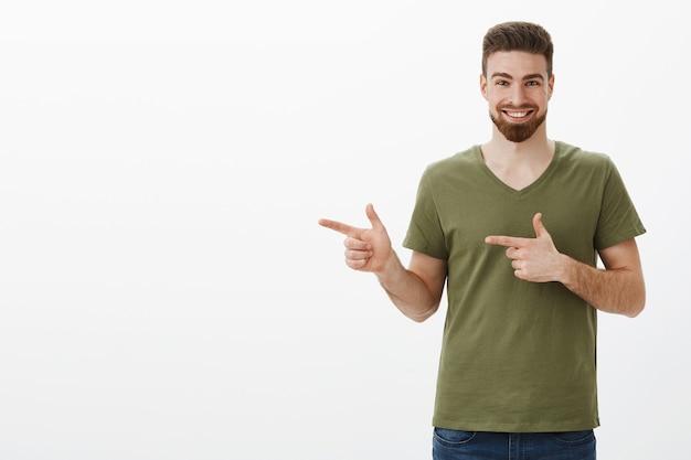 Yo check it out, schiet op. portret van een enthousiaste en opgewonden aantrekkelijke bebaarde man in olijfgroen t-shirt glimlachend opgetogen terwijl hij naar links wees met vingerpistolen om geweldig product over witte muur te laten zien