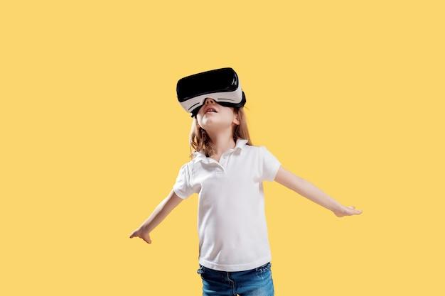 Yo van het meisje in formele uitrusting die vr-glazen het zetten draagt deelt in opwinding op geel wordt geïsoleerd uit. kind gebruikt een gaminggadget voor virtual reality. virtuele technologie