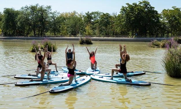 Yoga aan boord. jonge meisjes peddelen op sup-bord op het meer in de stad. groepsvrouwen beoefenen (doe) yoga, fitness, pilates en meditatie op een sup board. geweldige actieve training in de buitenlucht.