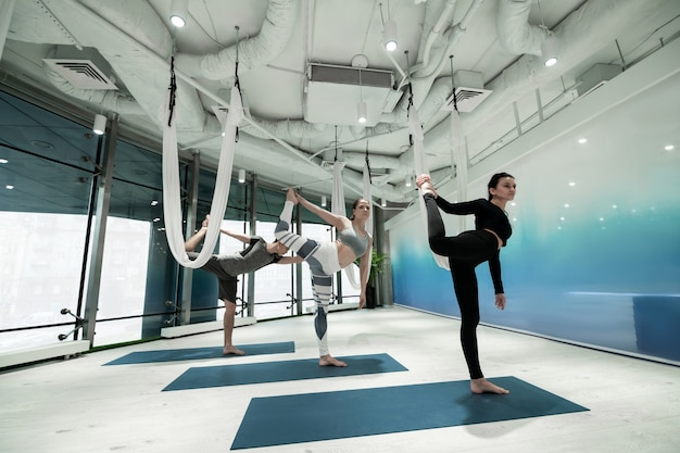 Yoga afmaken. twee vrouwen en een man staan op één been terwijl ze yoga afmaken met stretching