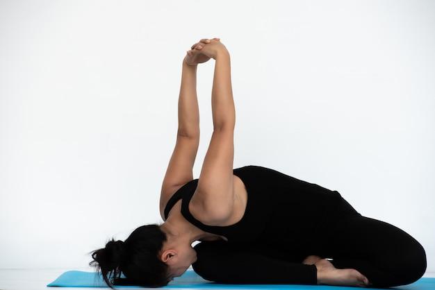 Yoga aziatische yoga vrouw doet thuis yoga pose.