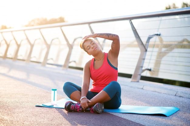 Yoga beoefenen. vrouwenzitting op sportmat terwijl het uitoefenen van yoga vroeg in de ochtend