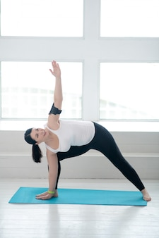 Yoga beoefening. donkerbruin wijfje dat zich op tapijt bevindt, dat haar lichaam uitrekt