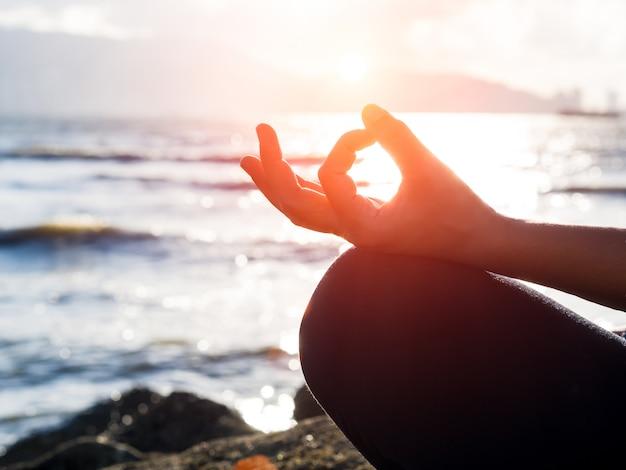 Yoga concept. de de hand van de close-upvrouw het praktizeren lotusbloem stelt op het strand bij zonsondergang.