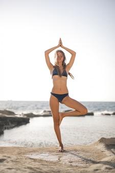Yoga doen op het strand