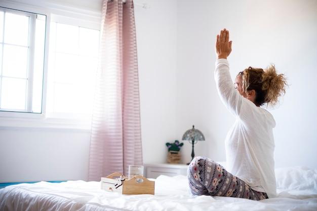Yoga en gezonde sport fitness activiteit thuis - concept van actieve mensen lockdown quarantaine - vrouw doet meditatie mindfulness in de slaapkamer voor het raam - helder wit
