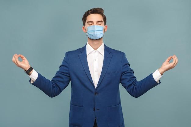 Yoga en meditatie jonge rustige man met chirurgisch medisch masker staan en ontspannen