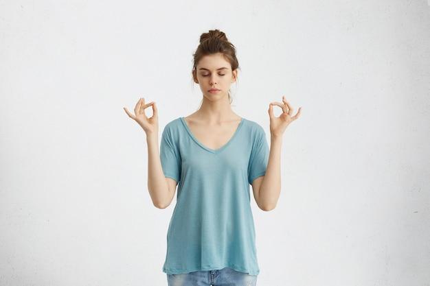 Yoga en meditatie. mooie terloops geklede jonge vrouw die de ogen gesloten houdt tijdens het mediteren, zich ontspannen, kalm en vredig voelt