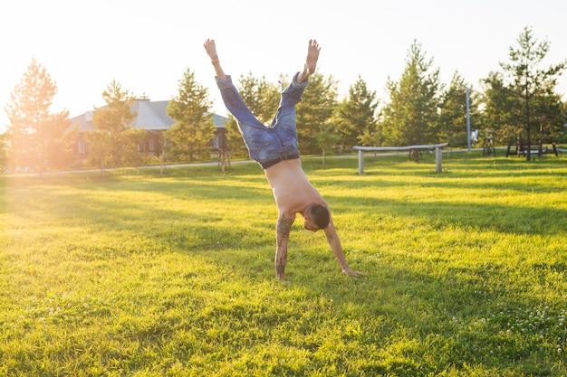 Yoga, fitness en gezonde levensstijl concept - man doet een handstand op de zomer natuur.