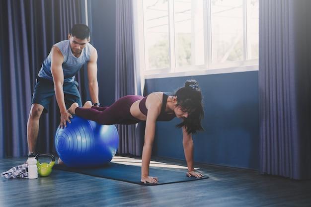 Yoga groepsconcept; jonge man vrouw het beoefenen van yoga in de klas onderwijzen; kalmte voelen en ontspannen in yogales