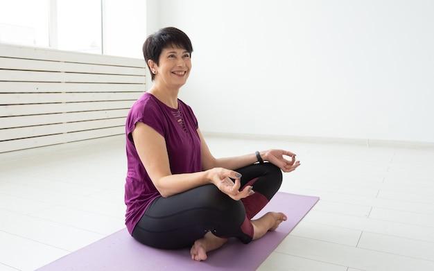 Yoga, harmonie, mensenconcept - vrouw van middelbare leeftijd die in lotuspositie zit.