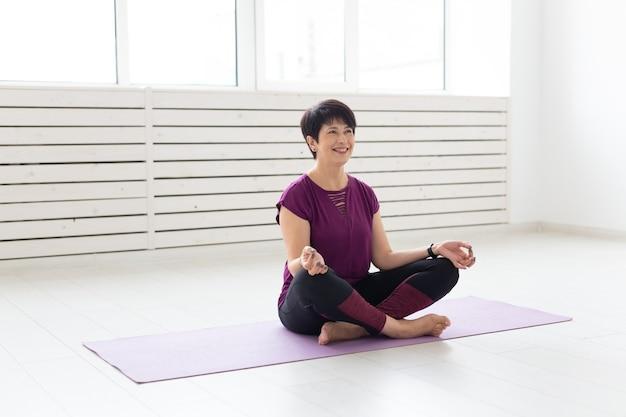Yoga, harmonie, mensenconcept. vrouw van middelbare leeftijd zitten in lotushouding.
