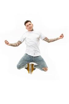 Yoga in beweging. mid-air shot van knappe gelukkige jonge man springen en poseren in asana tegen witte studio achtergrond. rennende man in beweging of beweging.