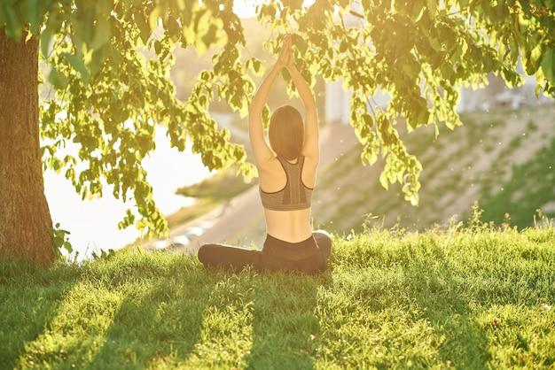 Yoga in het park met uitzicht op de rivier, met zonlicht. jonge vrouw in lotus positie zittend op het groene gras. het concept van rust en meditatie.