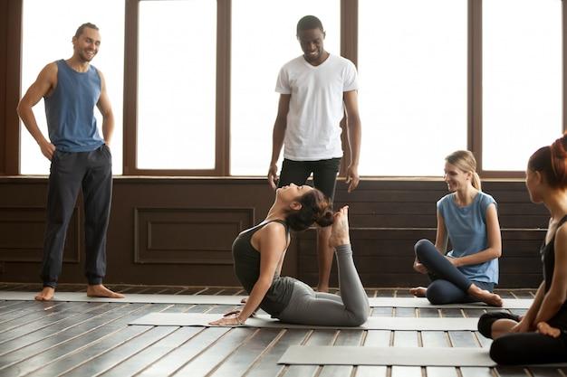 Yoga-instructeur die raja bhudjangasana geavanceerde oefening uitvoert
