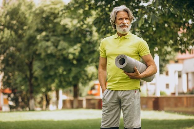 Yoga-instructeur van middelbare leeftijd met mat in park