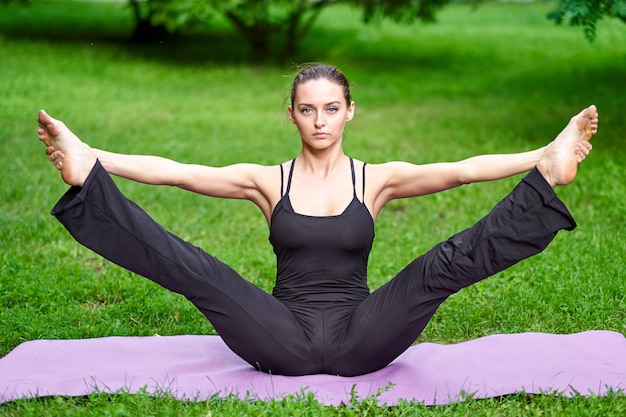 Yoga. jonge vrouw het beoefenen van yoga meditatie in de natuur in het park. gezondheid levensstijl concept