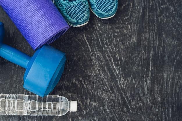 Yoga mat sportschoenen halters en fles water op blauwe achtergrond