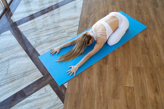 Yoga meisje in kind pose op de mat