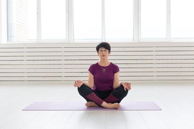 Yoga, mensen concept - een vrouw van middelbare leeftijd doet yoga in de sportschool