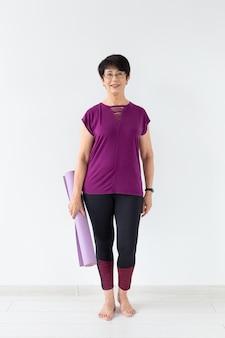 Yoga, mensen concept - portret van een vrouw van middelbare leeftijd na yoga met haar mat