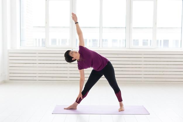 Yoga, mensenconcept - een vrouw van middelbare leeftijd die yoga doet en probeert om een asana te doen