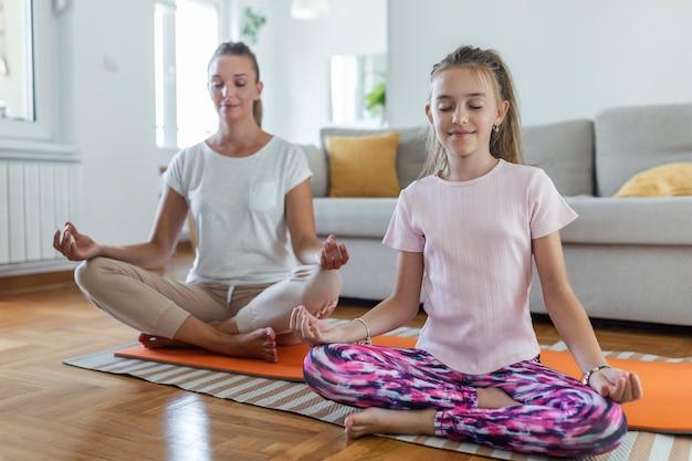 Yoga met kinderen. jonge familiemoeder en dochtertje mediteren met gesloten ogen terwijl ze in lotushouding zitten op de bloem in de woonkamer thuis