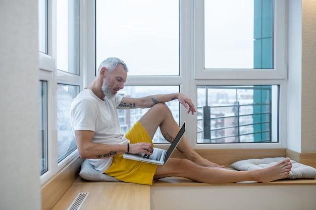 Yoga-online. een volwassen man in een wit t-shirt die op de grond zit en yoga doet op internet