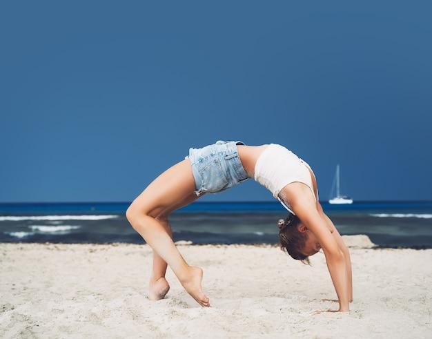 Yoga op het strand vrouw die yoga beoefent aan de kust van de oceaan