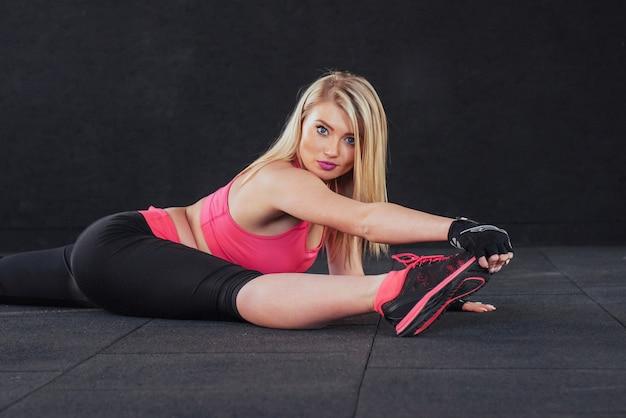 Yoga praktijk. meisje in fitness zaal voert uitrekken uit.