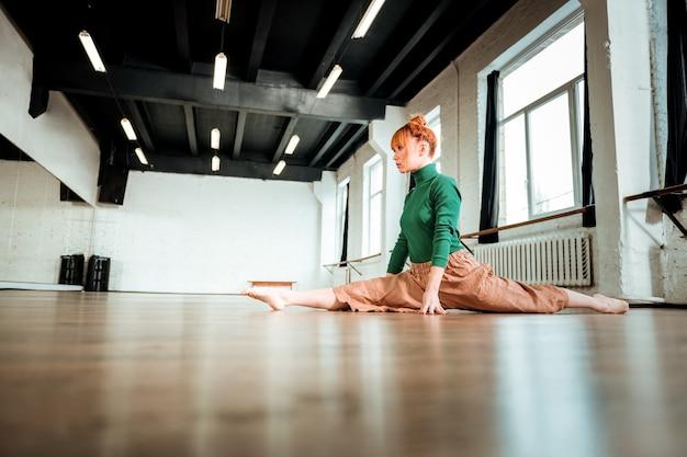 Yoga-stemming. professionele yoga-instructeur met rood haar die een groene coltrui draagt en er serieus uitziet tijdens het doen van een beenspleet
