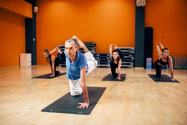 Yoga stretching training, vrouwelijke groep met instructeur, vetverbranding oefening, trainen in de sportschool. yogi binnen