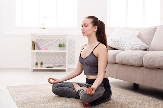 Yoga thuis vrouw doet lotus houding