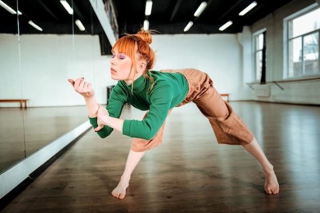 Yoga tijd. roodharige professionele yoga-instructeur die een groene coltrui draagt die zich in asana bevindt