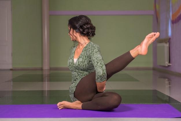 Yoga trainer uitvoeren van yoga houdingen in fitness klasse.