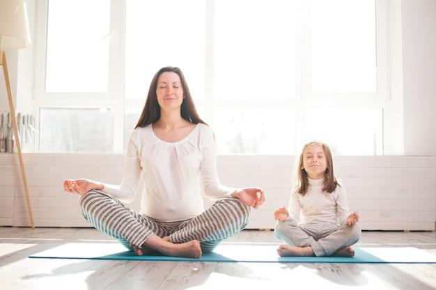 Yoga voor kinderen. vrouw doet yoga met haar kind