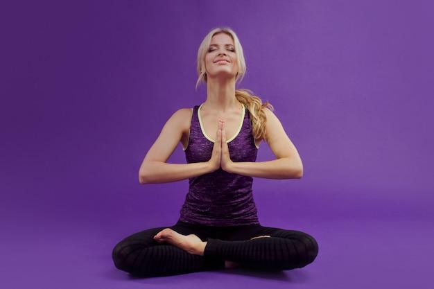 Yoga vormen. jonge sportieve vrouwen op paars