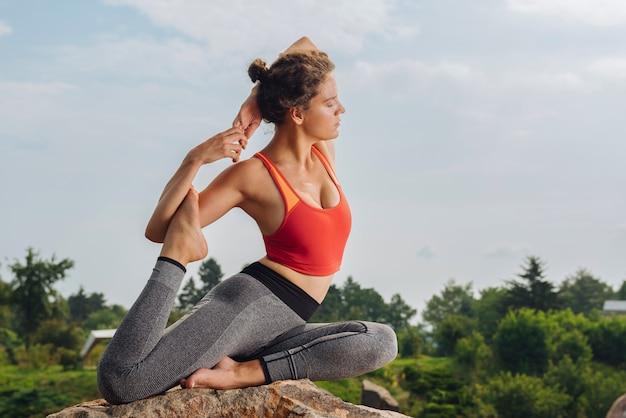 Yoga vrouw, gekleed in comfortabele sportkleding beoefenen van asana zittend op een rots in het bos