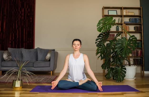 Yoga vrouw in een sport-uniform zit in een lotuspositie op de mat in een kamer thuis