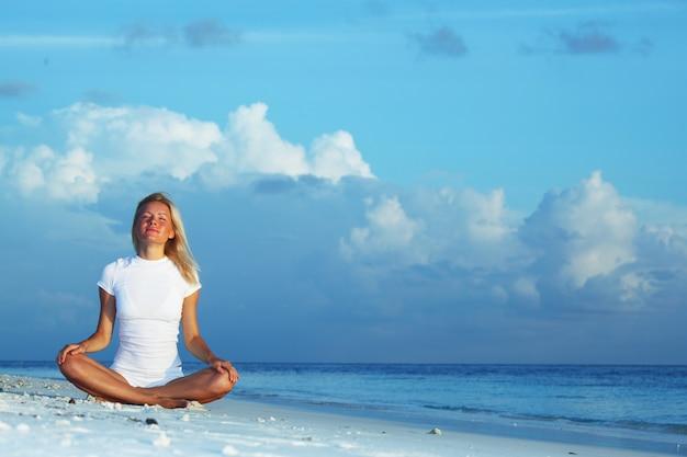 Yoga vrouw op zeekust
