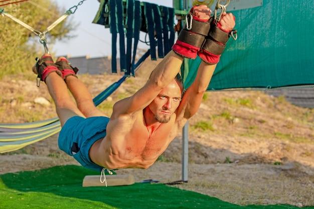 Yogabehandeling voor core yoga swing, slanke jongeman vastgebonden aan vier planken boven de vloer met oefenmat, man ontwikkelt uithoudingsvermogen en rekt core