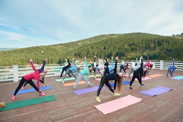 Yogagroep beoefent gedraaide driehoek.