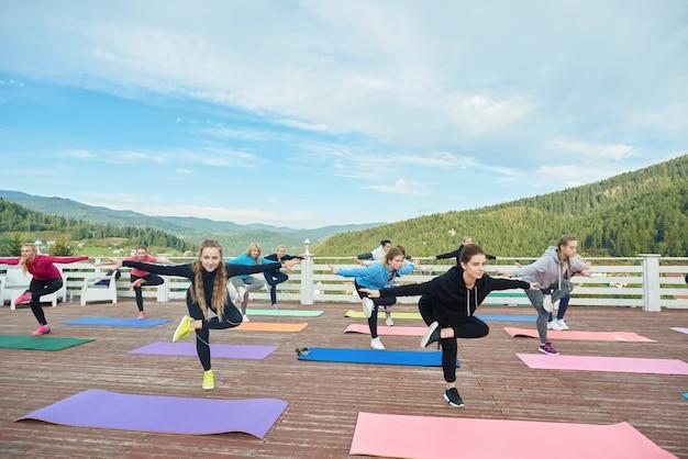 Yogagroep doet evenwichtsoefeningen op één been.