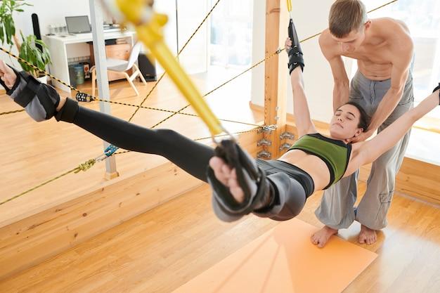 Yogainstructeur het aanpassen hals van vrouw het hangen op yogaschommeling