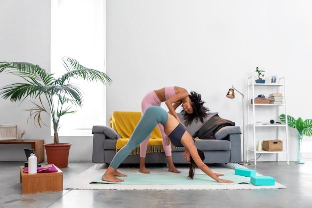 Yogaleraar corrigeert een naar beneden gerichte hondhouding voor haar student